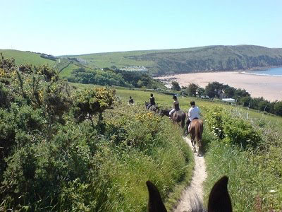 A line of horse riders, riding along a coastal path