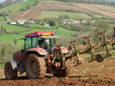 A tractor ploughing a steep field