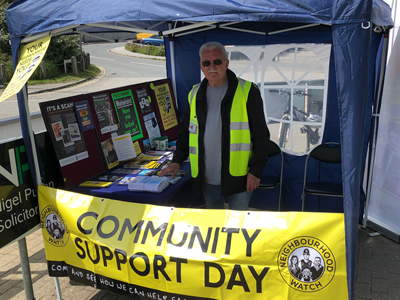 A person standing behind a stall with the banner community support day